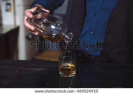 Businessman pouring whiskey in his glass