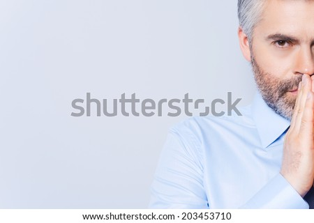 Businessman praying. Half face of concentrated mature man in shirt and tie holding hands clasped near face and looking away while standing against grey background - stock photo