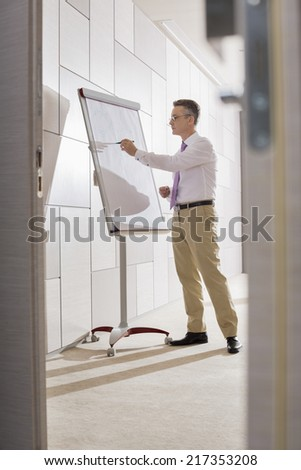 Businessman preparing for presentation on flipchart in office - stock photo