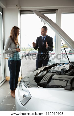 Businessman presenting a car to a woman in a garage - stock photo