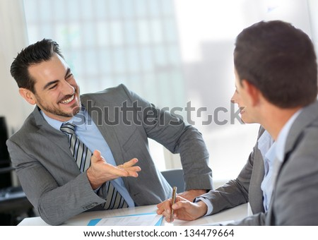 Businessman presenting contract to partners - stock photo