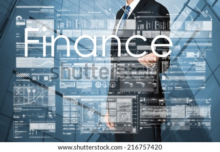 businessman presenting Finance text and graphs and diagrams with skyscraper in background - stock photo