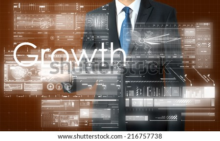 businessman presenting Growth text and graphs and diagrams with skyscraper in background - stock photo