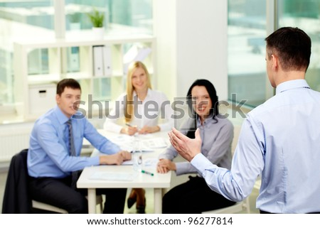 Businessman presenting new product or device to his smiling colleagues - stock photo