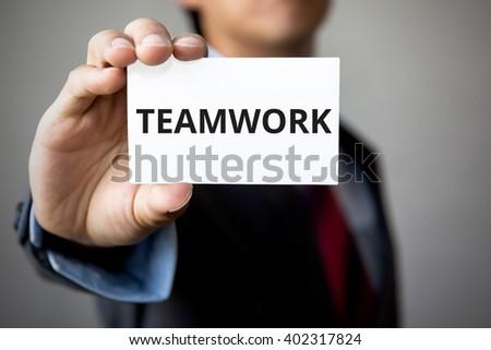 Businessman presenting 'TEAM WORK' word on white card - stock photo