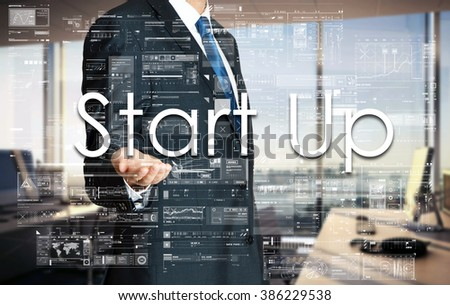 Businessman presenting text Start Up on virtual screen. He is in the office - stock photo