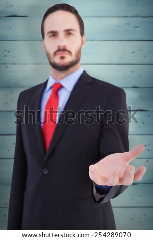 Businessman presenting with his hand against wooden planks - stock photo