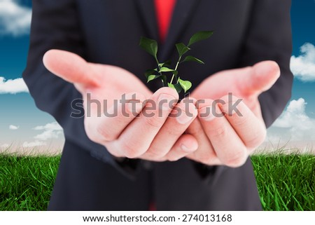 Businessman presenting with his hands against green field under blue sky