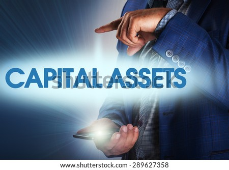 Businessman presses button capital assets on virtual screens. Business, technology, internet and networking concept. - stock photo