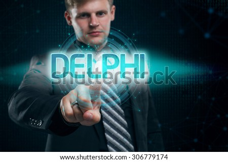 Businessman presses button delphi on virtual screens. Business, technology, internet and networking concept. - stock photo