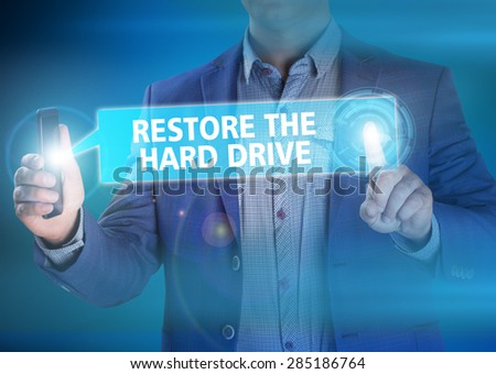 Businessman presses button restore hard drive on virtual screens. Business, technology, internet and networking concept. - stock photo