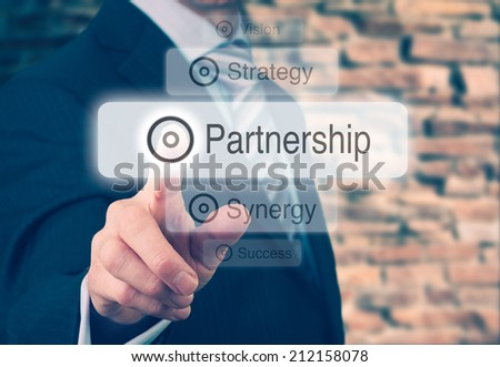Businessman pressing a Partnership concept button. Instagram styling applied. - stock photo