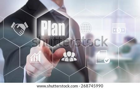 Businessman pressing a Plan concept button. - stock photo