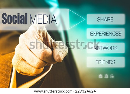 Businessman pressing a Social Media concept button. Instagram Styling Applied. - stock photo