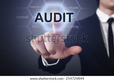 businessman pressing audit button on virtual screens. business concept - stock photo