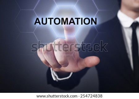businessman pressing automation button on virtual screens. business concept - stock photo