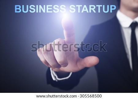 """Businessman pressing button on touch screen interface and select """"Business startup"""". Business concept. Internet concept. - stock photo"""