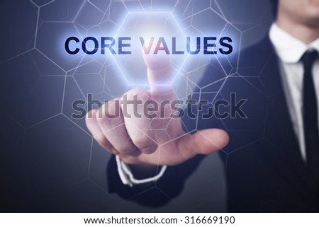 "Businessman pressing button on touch screen interface and select ""core values""."