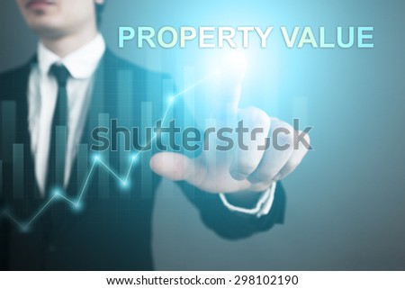 Businessman pressing button on touch screen interface and select Property value. Business concept. - stock photo