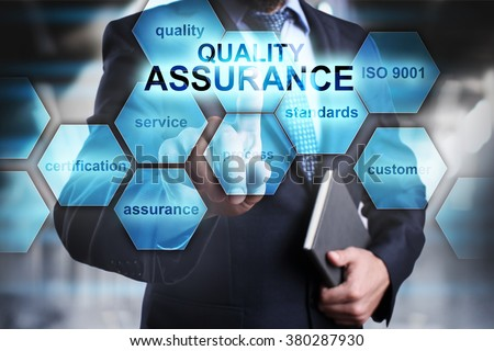 """Businessman pressing button on touch screen interface and select """"Quality assurance"""". Business concept. Internet and technology concept. - stock photo"""