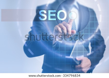 Businessman pressing button on touch screen interface and select SEO. Business, internet, technology concept. - stock photo