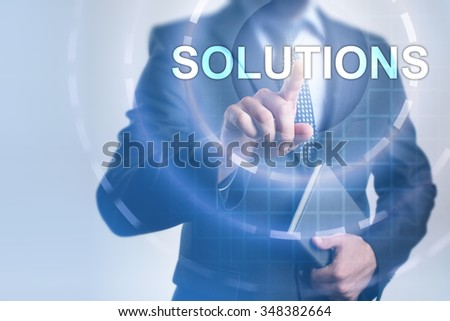 Businessman pressing button on touch screen interface and select Solutions. Business, internet, technology concept. - stock photo
