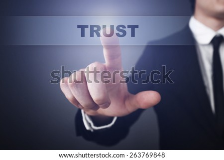 Businessman pressing button on touch screen interface and select  trust. Business concept. - stock photo