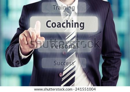 Businessman pressing coaching button. Coaching concept, toned photo. - stock photo