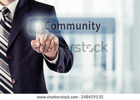 Businessman pressing Community button at his office. Toned photo. - stock photo