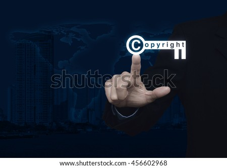 Businessman pressing copyright key icon over map and city tower background, Copyright and patents concept, Elements of this image furnished by NASA