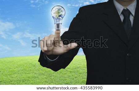 Businessman pressing earth globe in light bulb over green grass field with blue sky, Energy conservation and environmental concept, Elements of this image furnished by NASA - stock photo