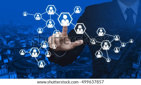 Businessman pressing network icon over city tower and street blue tone background, Communication business concept