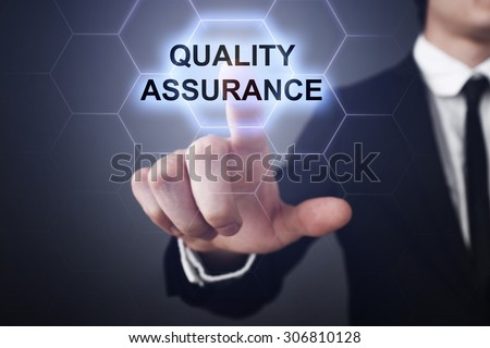"""Businessman pressing touch screen interface and select icon """"quality assurance"""". Business concept. Internet concept. - stock photo"""