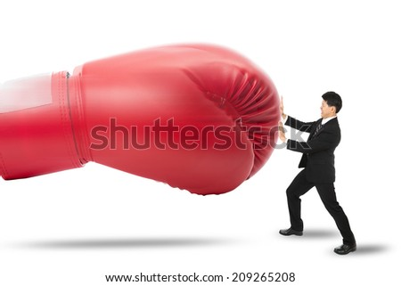 Businessman protect himself by push red glove punch him with white background - stock photo