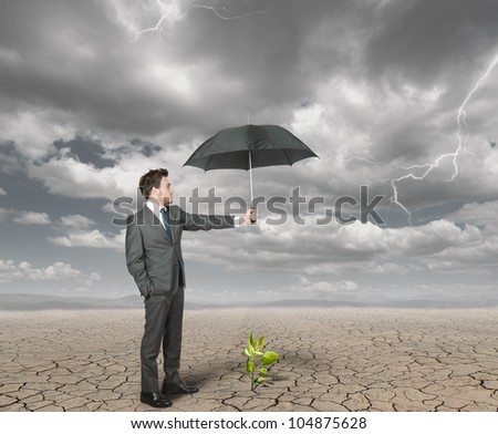 Businessman protect with umbrella a plant to help the agriculture - stock photo