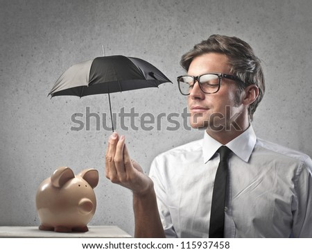 Businessman protecting a piggy with a little black umbrella - stock photo