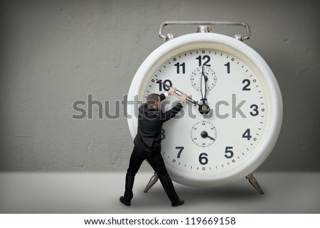 Businessman pulling a clock hand backwards - stock photo