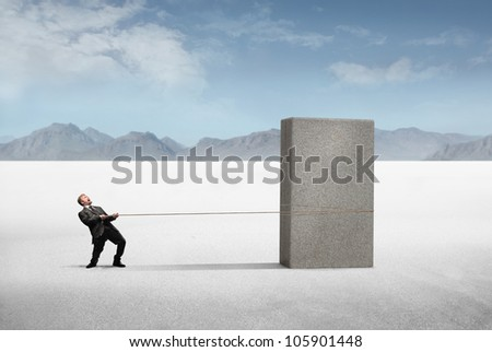 Businessman pulling a heavy block of stone in a desert