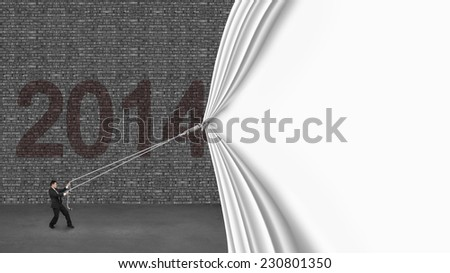 businessman pulling down white blank curtain covering old 2014 brick wall on gray concrete floor - stock photo