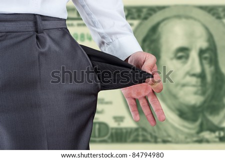 Businessman pulling empty pocket out of pants against dollar banknote - stock photo