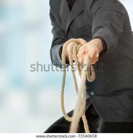 Businessman pulling on a rope. - stock photo