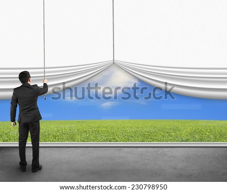 businessman pulling open white blank curtain discovered natural sky meadow on concrete floor - stock photo