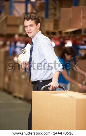 Businessman Pulling Pallet In Warehouse - stock photo