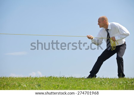 Businessman pulling rope in park - stock photo