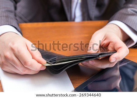 Businessman pulls from his wallet dollars