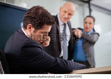 Businessman punching his colleague in the face at a meeting. Businesswoman is trying to stop the fight. - stock photo