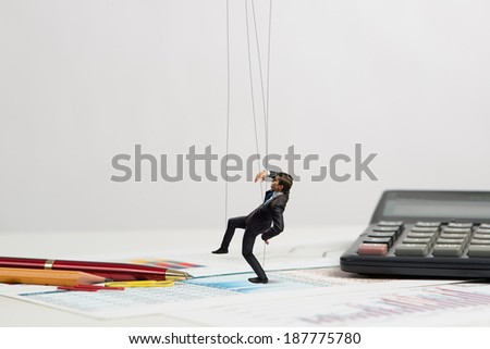 businessman puppet doll is on the desk, past the stationery items - stock photo