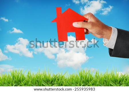 businessman push a house model on blue sky,Real estate concept