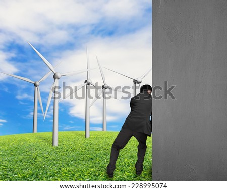 businessman push away concrete wall with nature sky clouds grass and groups of wind turbines