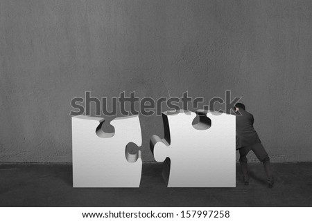 Businessman push two heavy puzzles together in concrete wall background - stock photo